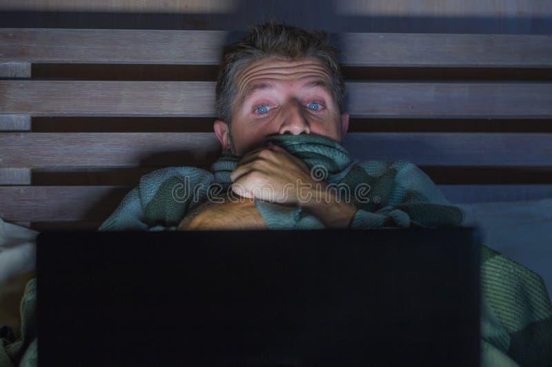 Homem assustado e forçado dos jovens no filme de terror de observação do Internet da cama tardio com laptop ou televisão do quart imagem de stock