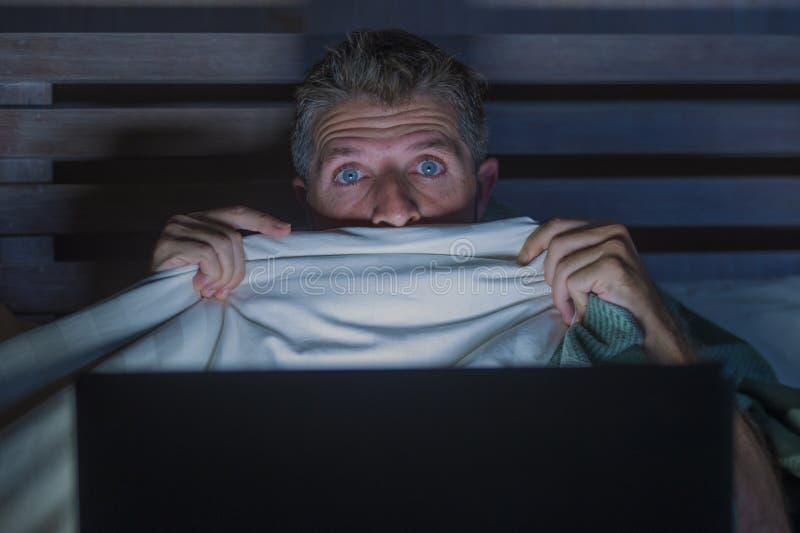 Homem assustado e forçado dos jovens no filme de terror de observação do Internet da cama tardio com laptop ou televisão do quart imagem de stock royalty free