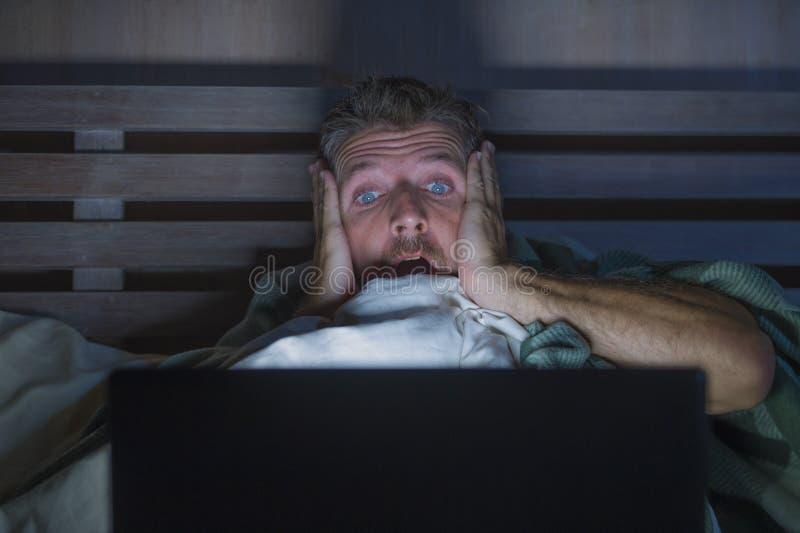 Homem assustado e forçado dos jovens no filme de terror de observação do Internet da cama tardio com laptop ou televisão do quart fotografia de stock royalty free