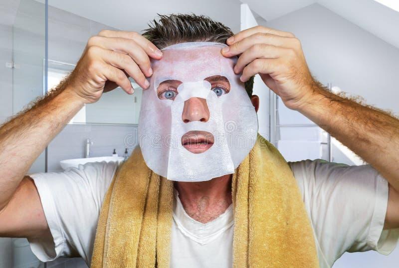 Homem assustado e surpreendido novo em casa que usa a m?scara facial do papel da beleza que limpa fazendo o tratamento facial ant fotografia de stock royalty free