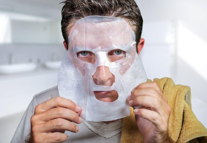 Homem assustado e surpreendido novo em casa que usa a m?scara facial do papel da beleza que limpa fazendo o tratamento facial ant fotos de stock
