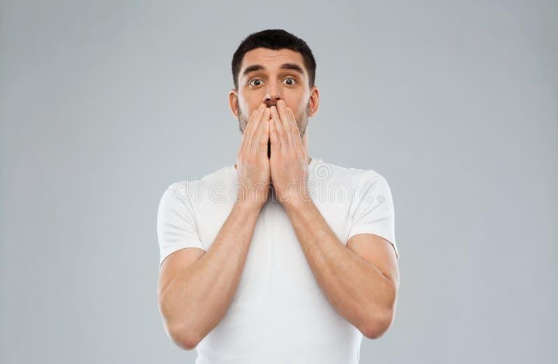 Homem assustado no t-shirt branco sobre o fundo cinzento imagem de stock royalty free