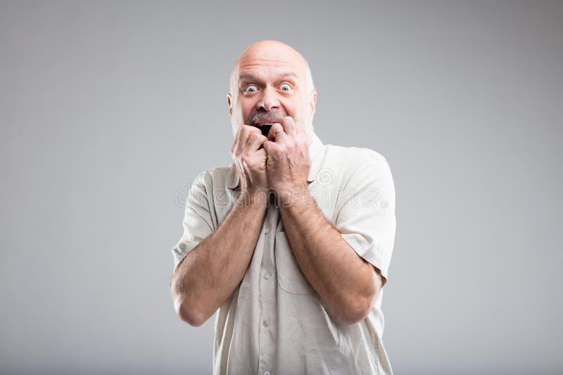 Homem assustado que morde seus pregos devido ao medo imagem de stock