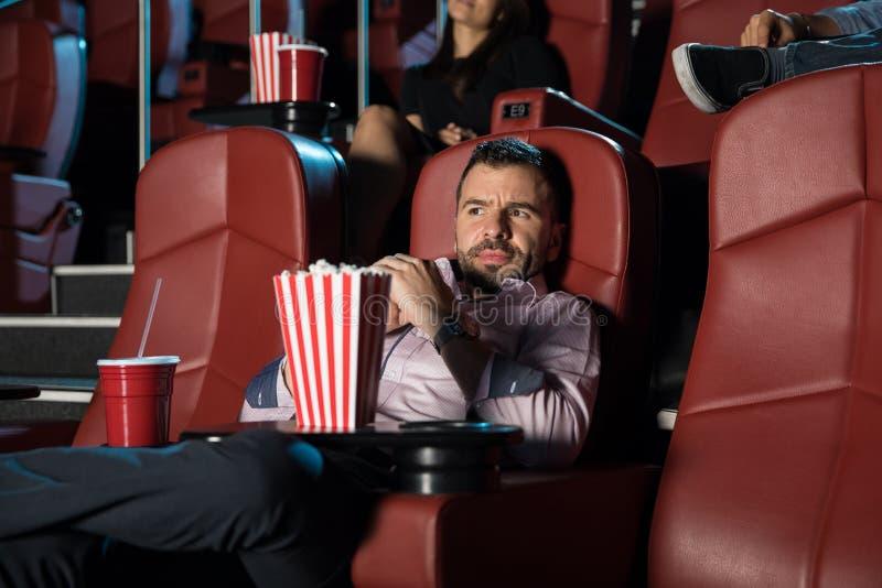 Homem assustado que olha um filme de terror imagens de stock royalty free