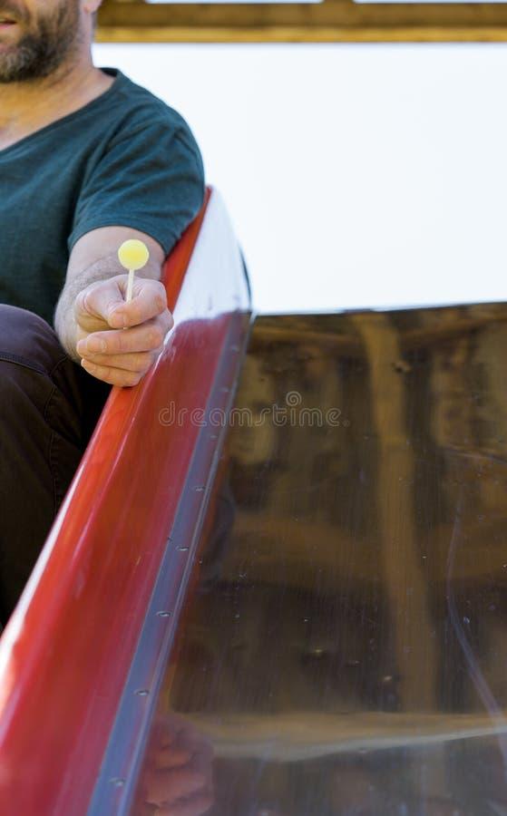 Homem assustador com um pirulito de oferecimento dos doces da barba às crianças em um campo de jogos fotos de stock
