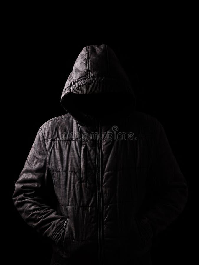 Homem assustador e assustador que esconde nas sombras, com a cara e a identidade escondidas com a capa fotografia de stock royalty free