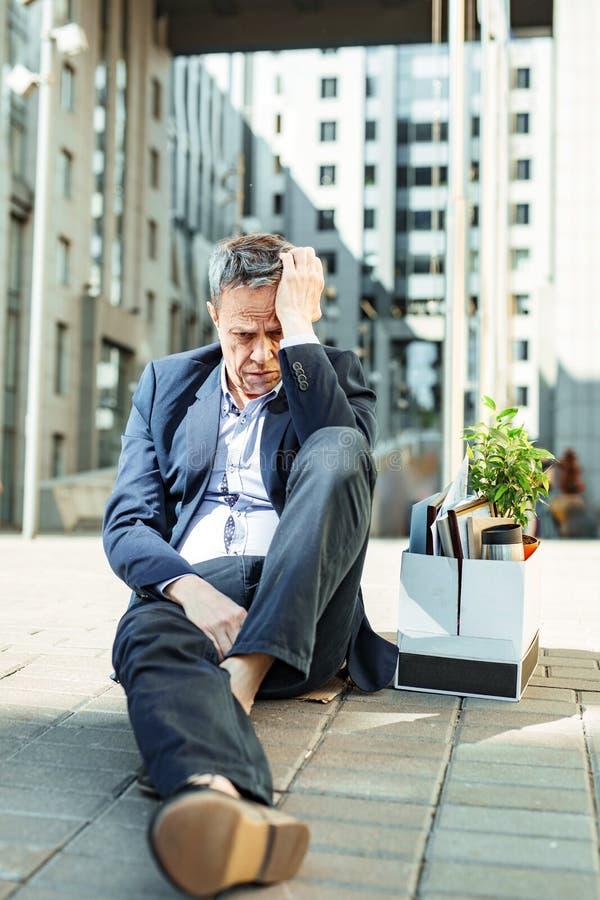 Homem ateado fogo que veste o terno preto que senta-se no assoalho fora do escritório fotos de stock royalty free