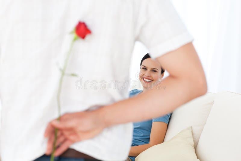 Homem atento que esconde uma flor imagem de stock