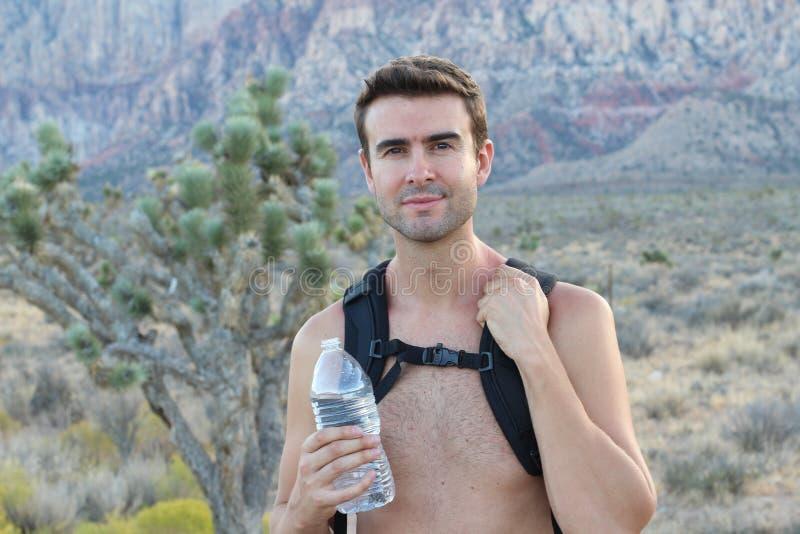 Homem ativo que trekking ao longo do deserto, andando apenas nas montanhas rochosas secas, descobrindo a natureza, expedição à re fotografia de stock royalty free