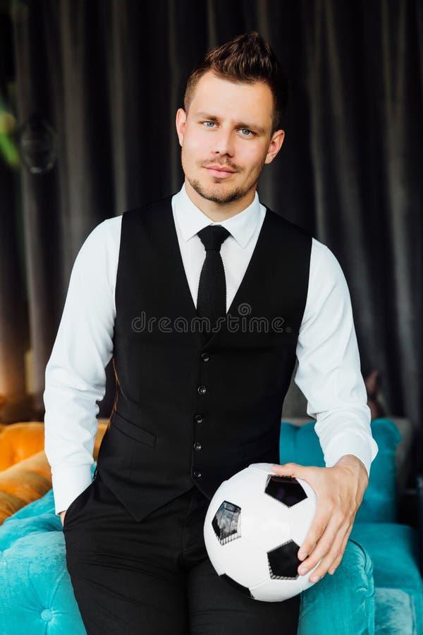 Homem atlético à moda em uma veste do traje do negócio que guarda uma bola de futebol Jogador de futebol imagens de stock