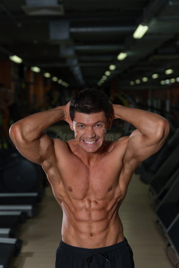 Homem atlético bronzeado com corpo muscular, vista dianteira imagens de stock royalty free