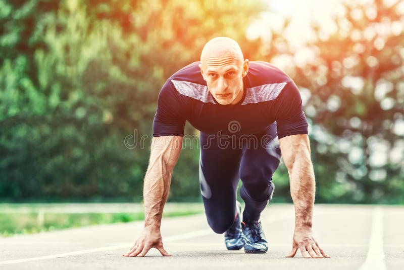 Homem atlético calvo na posição e na vista de começo corredor na distância no estádio imagem de stock royalty free