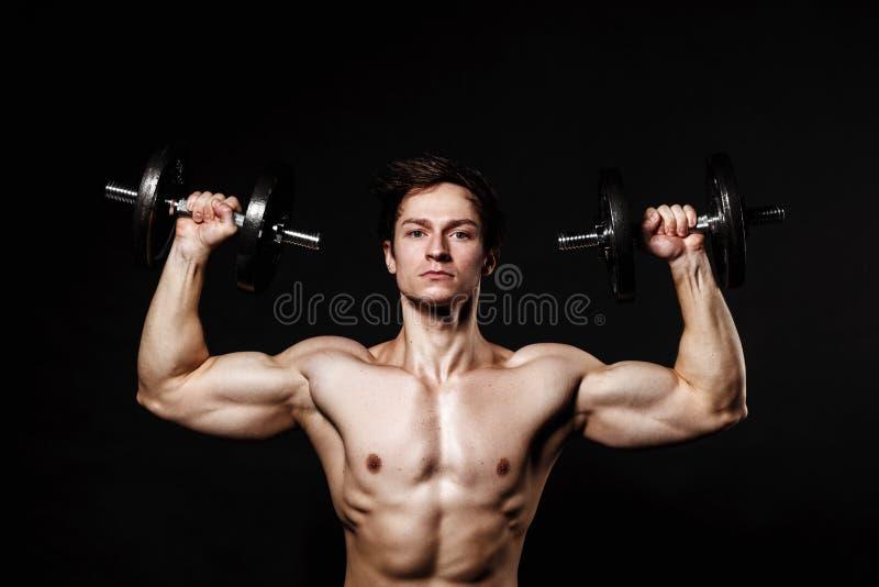 Homem atlético considerável com os pesos que olham seguramente para a frente fotos de stock