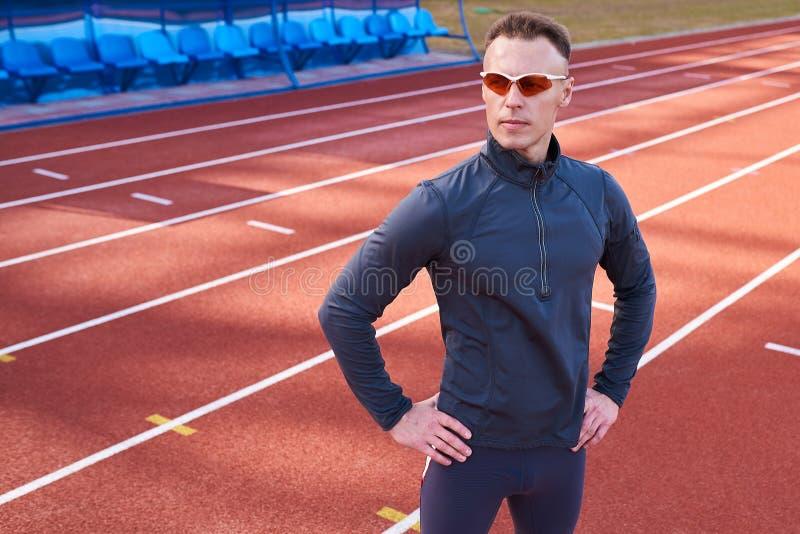 Homem atlético considerável que levanta na pista de atletismo do estádio imagens de stock royalty free