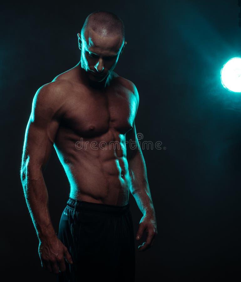 Homem atlético descamisado que olha para baixo com projetor fotografia de stock royalty free