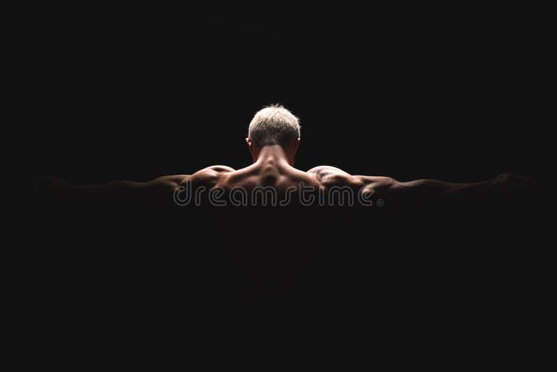 Homem atlético do poder considerável na luz dramática Halterofilista forte com ombros perfeitos, bíceps, tríceps, parte traseira, foto de stock