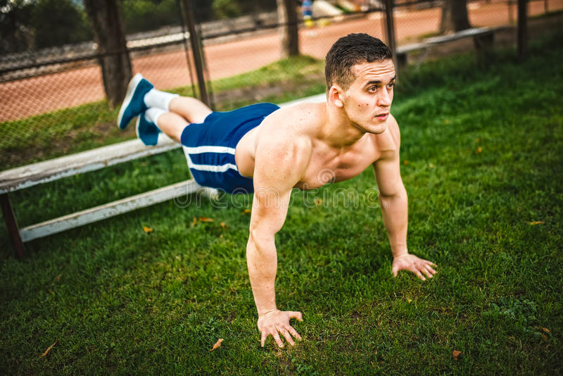 Homem atlético durante o exercício no parque Instrutor pessoal da aptidão que faz flexões de braço na grama conceito do treinamen imagem de stock royalty free