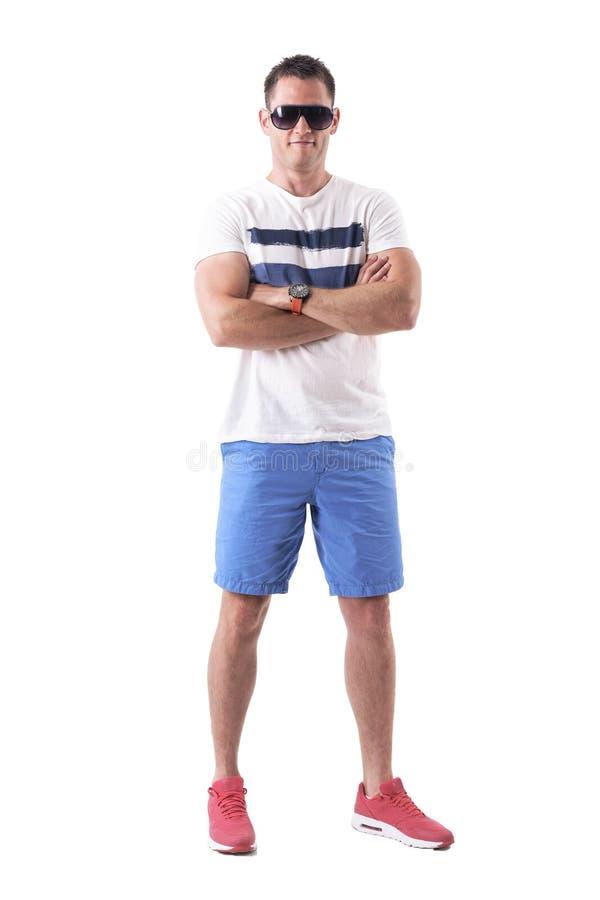 Homem atlético forte na roupa do verão com óculos de sol e os braços cruzados imagens de stock