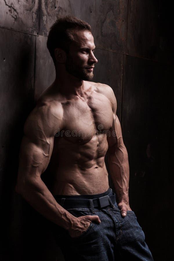 Homem atlético forte no fundo escuro do grunge fotos de stock