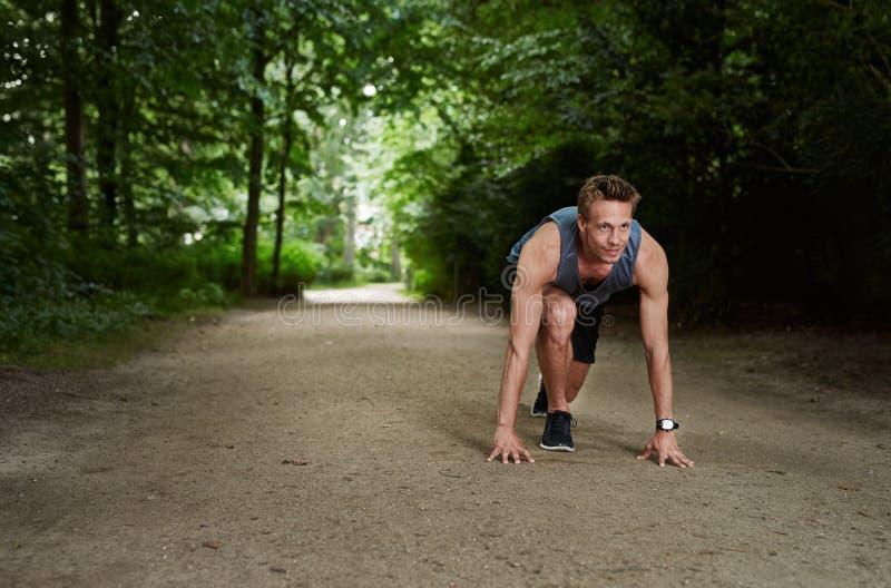 Homem atlético na posição de começo corredor no parque fotografia de stock royalty free