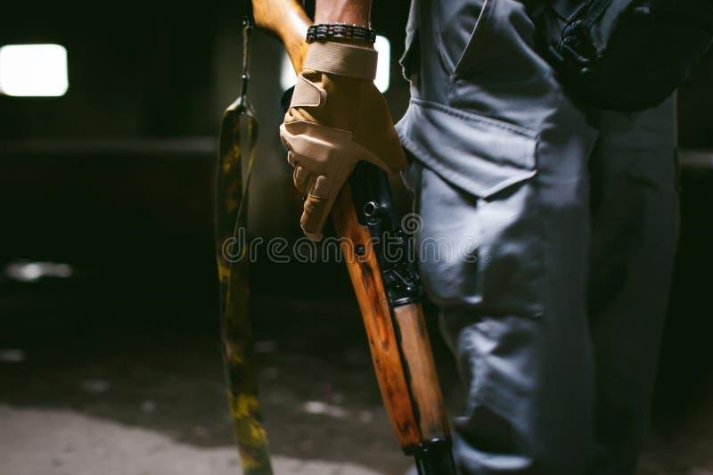 Homem atlético na roupa cinzenta com uma arma da carabina em sua mão fotos de stock royalty free