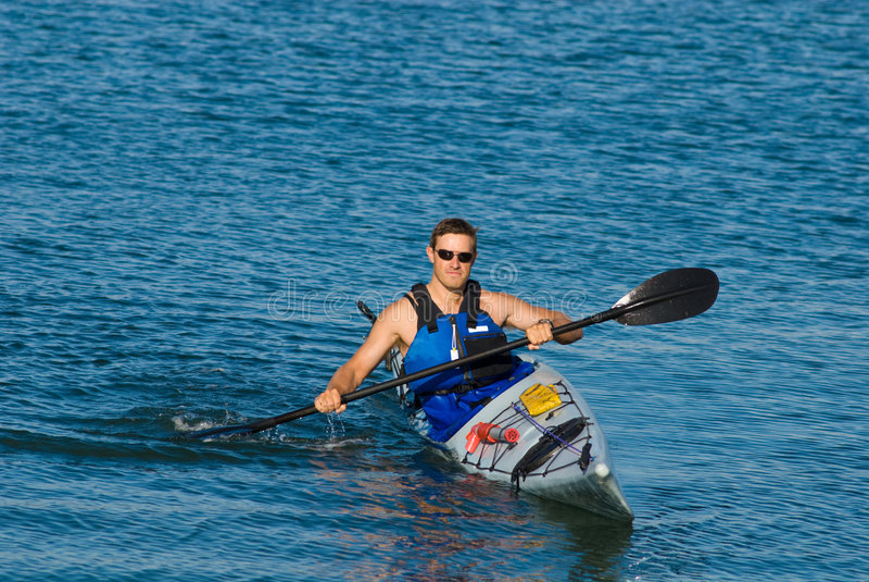 Homem atlético no caiaque do mar imagem de stock