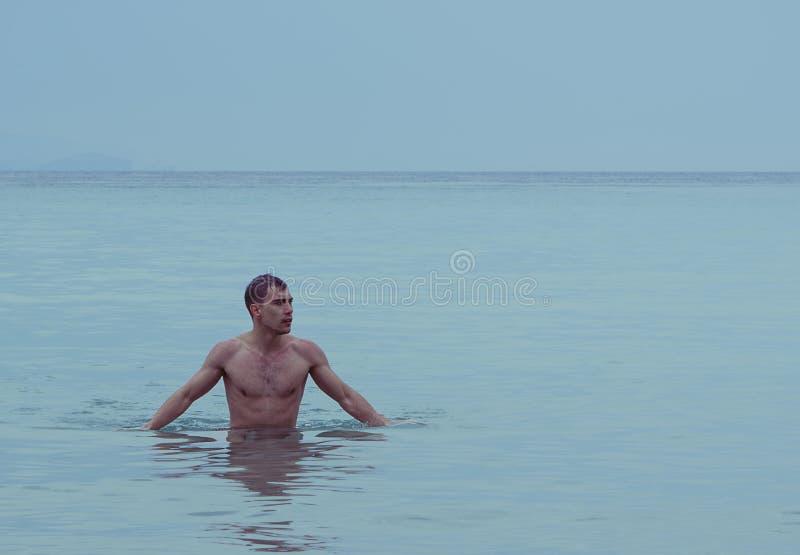 Homem atlético novo atrativo no mar ou no oceano que mostram o torso muscular despido imagens de stock