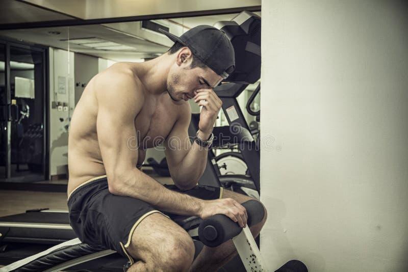 Homem atlético novo considerável que descansa no gym imagens de stock