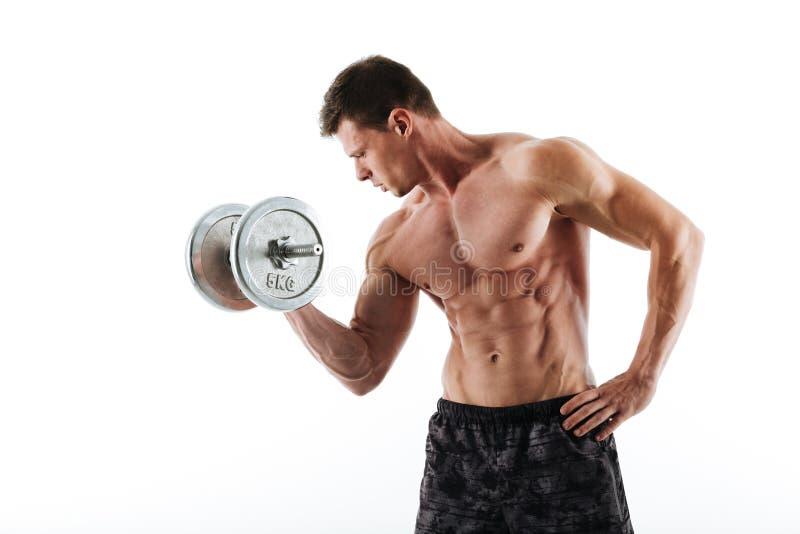 Homem atlético novo em topless que dá certo com peso pesado imagem de stock