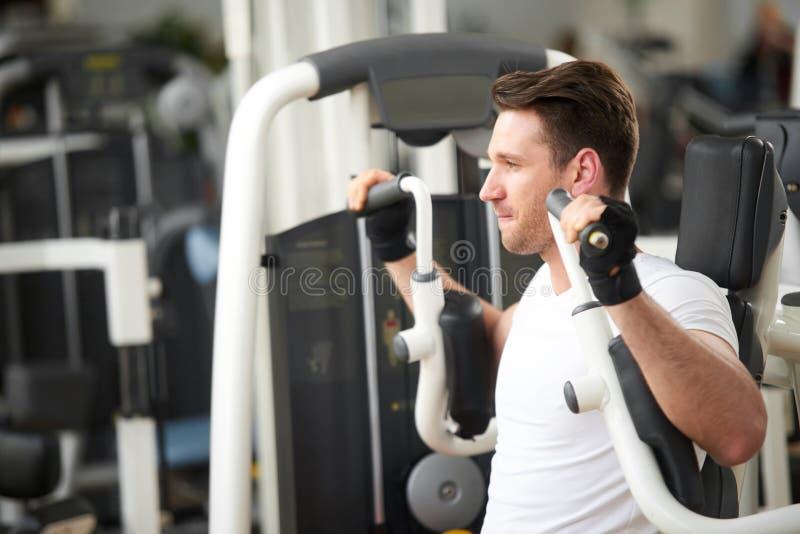 Homem atlético novo que dá certo no gym foto de stock