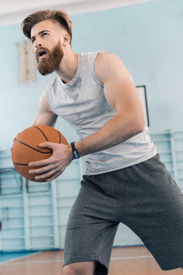 Homem atlético novo que joga o basquetebol no centro de esportes fotos de stock royalty free