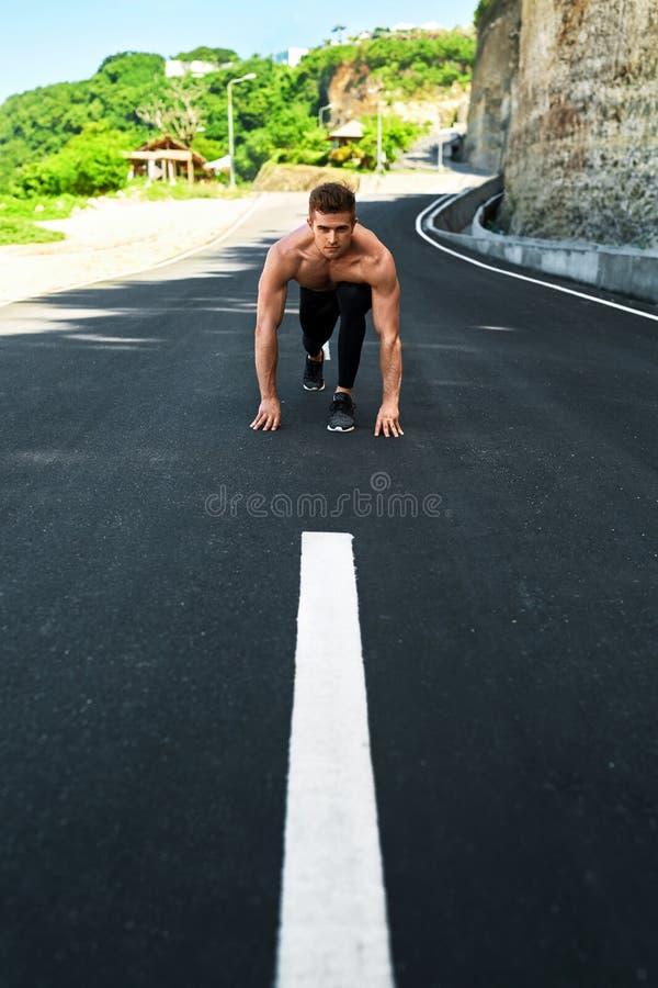 Homem atlético pronto para começar correr fora Conceito do exercício dos esportes fotos de stock royalty free
