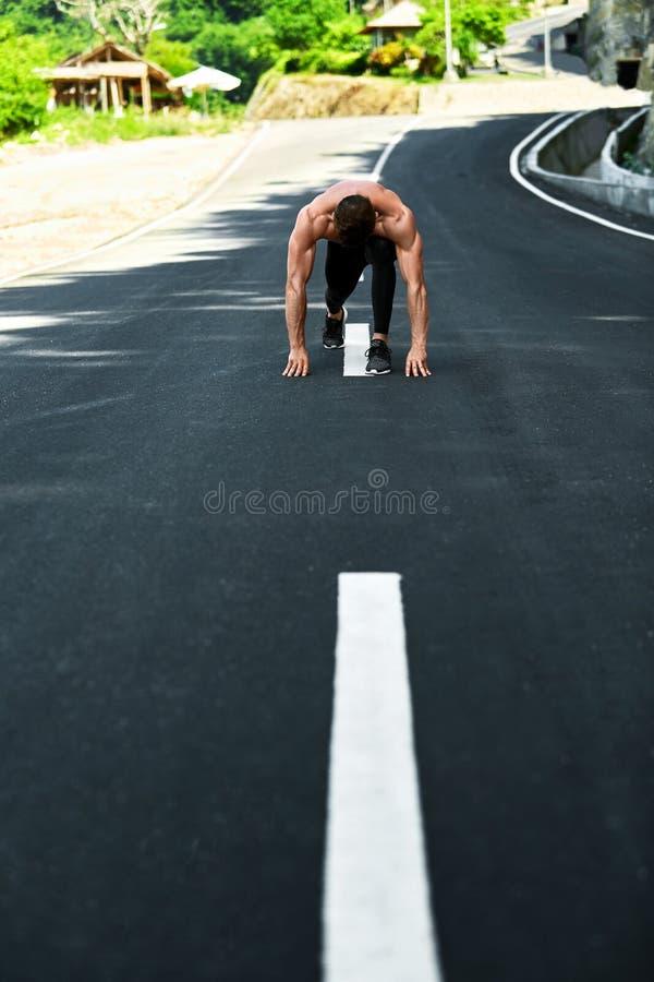 Homem atlético pronto para começar correr fora Conceito do exercício dos esportes fotografia de stock