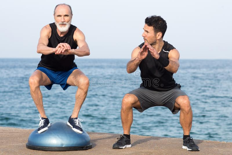 Homem atlético que faz um exercício da etapa com o treinador na plataforma do equilíbrio fotos de stock