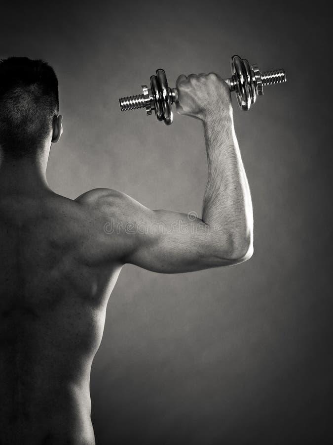 Homem atlético que trabalha com pesos pesados imagem de stock