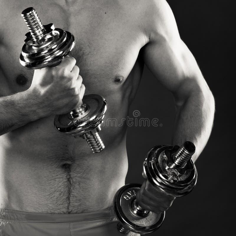 Homem atlético que trabalha com pesos pesados fotografia de stock
