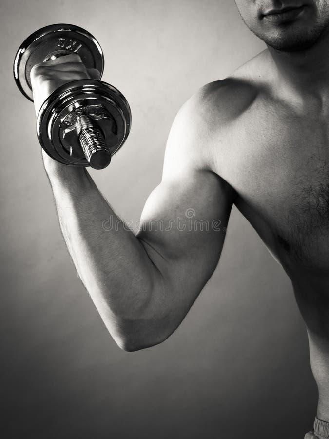 Homem atlético que trabalha com pesos pesados fotografia de stock royalty free