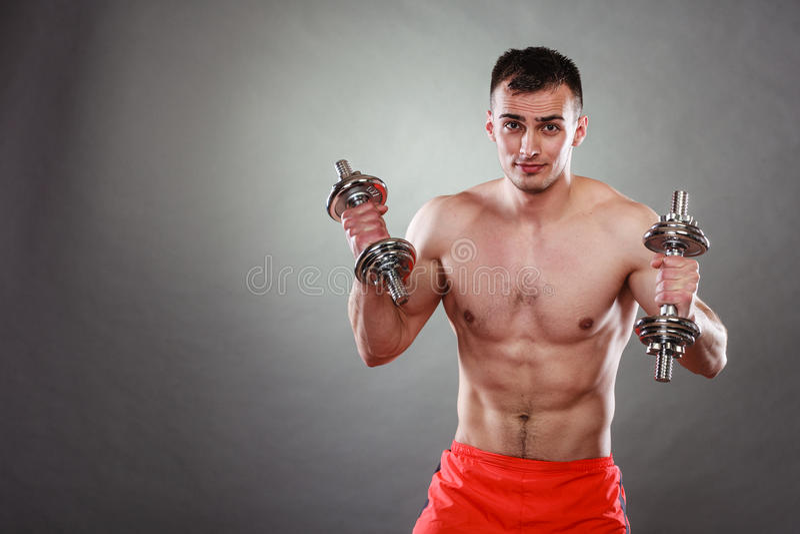 Homem atlético que trabalha com pesos pesados imagens de stock royalty free
