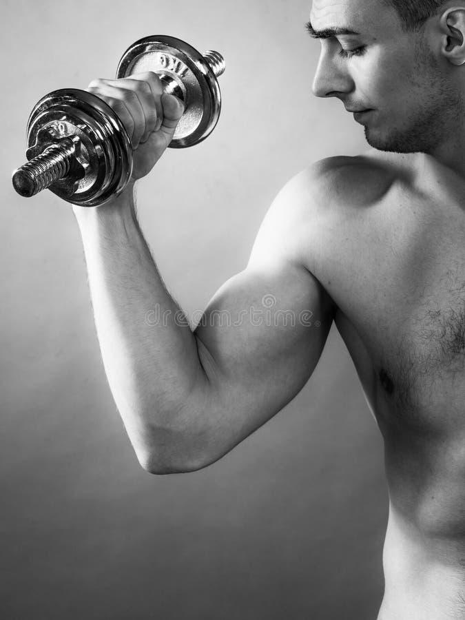 Homem atlético que trabalha com pesos pesados imagens de stock