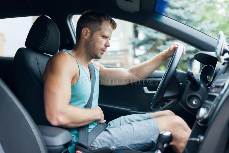 Homem atrás do volante com dor de estômago imagens de stock