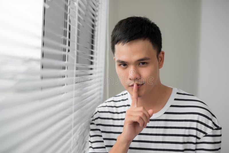 Homem atrativo com o dedo nos bordos que fazem o gesto do sil?ncio shh imagem de stock
