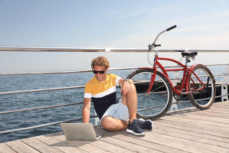 Homem atrativo com portátil e bicicleta perto do mar fotos de stock royalty free