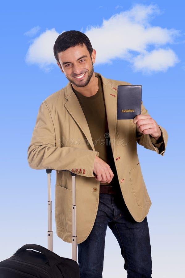 Homem atrativo do viajante que inclina-se na caixa da bagagem que mantém o sorriso do passaporte feliz e seguro imagens de stock royalty free