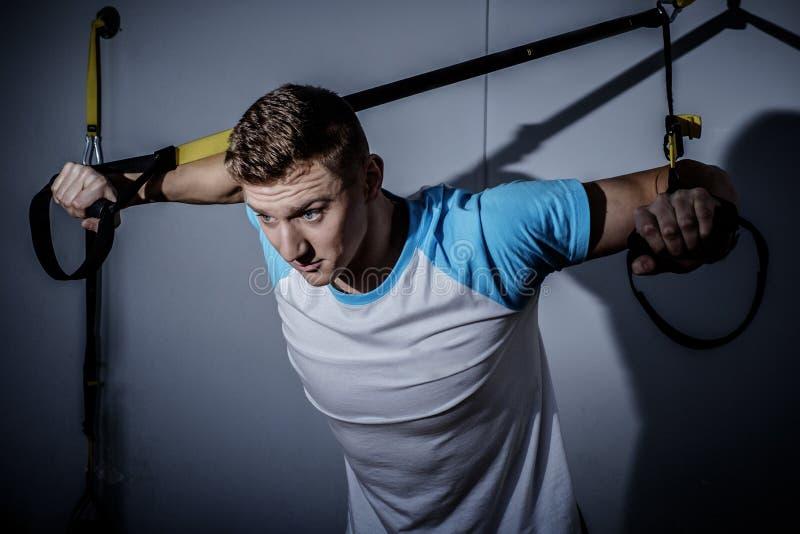 Homem atrativo durante o exercício com as correias da suspensão no Gym fotografia de stock royalty free