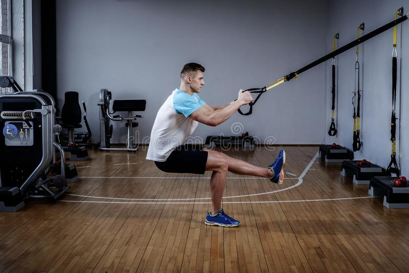 Homem atrativo durante o exercício com as correias da suspensão no Gym imagens de stock royalty free