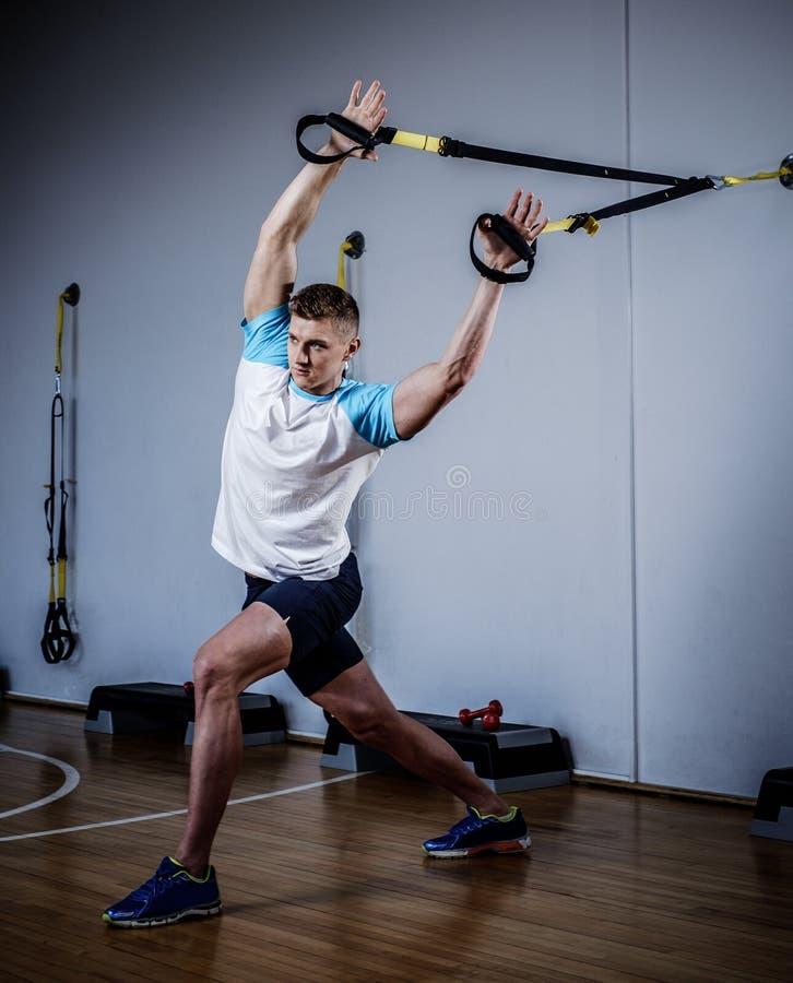 Homem atrativo durante o exercício com as correias da suspensão no Gym imagem de stock