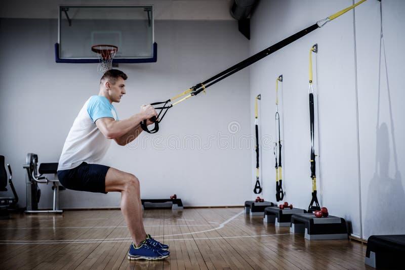 Homem atrativo durante o exercício com as correias da suspensão no Gym imagens de stock