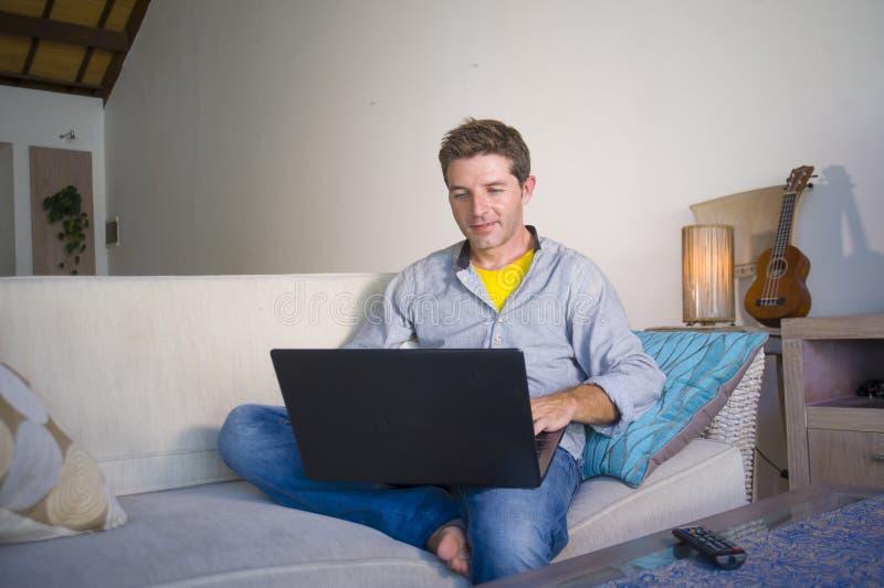 Homem atrativo e bem sucedido novo que trabalha da sala de visitas home que senta-se em trabalhos em rede do sofá no laptop feliz imagem de stock royalty free
