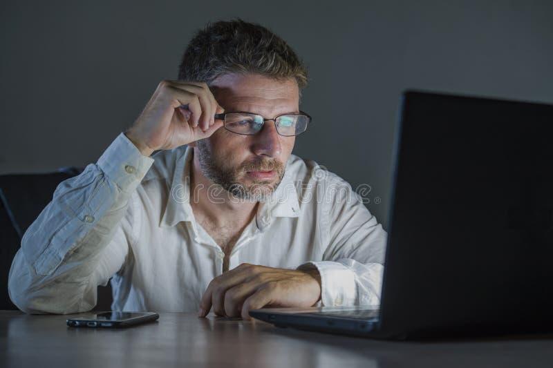 Homem atrativo e cansado do empresário do viciado em trabalho no laptop de utilização tardio do trabalho de vidros que troca no m imagens de stock