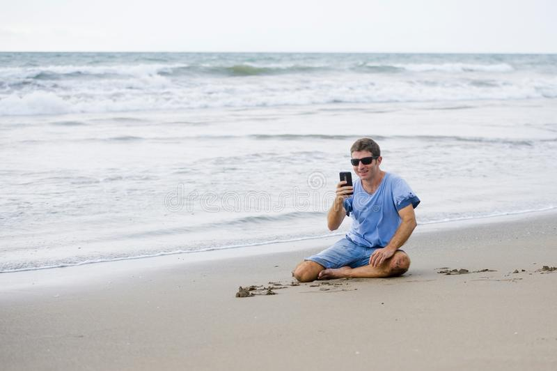 Homem atrativo e considerável em seu 30s que senta-se na areia relaxado na praia que ri na frente do mar que texting no pho móvel fotos de stock royalty free